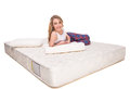 Mattress young smiling woman is lying on the quality and looking at the camra over white background Royalty Free Stock Photo