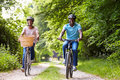 Mature african american couple on cycle ride in countryside looking to camera smiling Stock Photos
