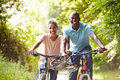 Mature african american couple on cycle ride in countryside smiling to camera with helmet hanging handle Royalty Free Stock Image