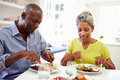 Mature african american couple eating meal at home sitting table Stock Photo
