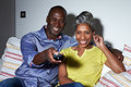 Mature african american couple on sofa watching tv together using remote control smiling Royalty Free Stock Image