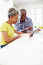 Mature african american couple using digital table tablet at home in kitchen at breakfast Stock Photos