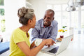 Mature african american couple using laptop at bre breakfast in kitchen smiling each other Stock Photography