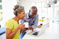 Mature african american couple using laptop at bre breakfast in kitchen whilst holding a hot drink Stock Image