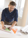 Mature architect working on blueprint at desk handsome male in office Stock Photography