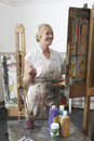 Mature artist painting in art studio smiling female at easel Stock Photos