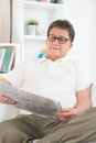 Mature asian man reading newspaper portrait of on sitting on sofa at home senior retiree indoors living lifestyle Royalty Free Stock Photo