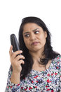 Mature asian woman annoyed and frustrated at unwanted phone calls isolated on white Royalty Free Stock Photo