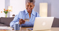 Mature black woman happily paying her bills sitting at desk Royalty Free Stock Image