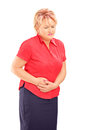 Mature blond female suffering from a stomach ache isolated on white background Stock Photography