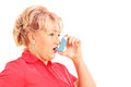 Mature blond woman taking asthma treatment isolated on white background Stock Images