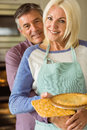 Mature blonde holding fresh pie with husband hugging her at home in the kitchen Stock Photo