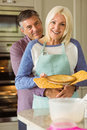 Mature blonde holding fresh pie with husband hugging her at home in the kitchen Stock Image