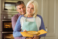 Mature blonde holding fresh pie with husband hugging her at home in the kitchen Stock Photography