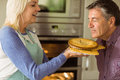 Mature blonde holding fresh pie with husband kissing her at home in the kitchen Royalty Free Stock Photos