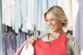 Mature blonde woman shopping in clothes shop holding red vest top on coathanger smiling Royalty Free Stock Image