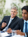 Mature business man with cell phone at a meeting Royalty Free Stock Image