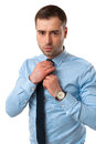 Mature business man corrects his tie on white isolated background Royalty Free Stock Images