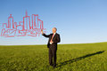 Mature businessman drawing buildings in field full length of against sky Stock Photo