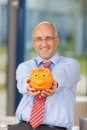 Mature businessman holding piggy bank in office portrait of smiling Stock Photos