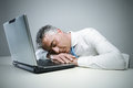 Mature businessman sleeping on his laptop Royalty Free Stock Photography