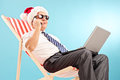Mature businessman talking on phone in a sun lounger seated blue background Royalty Free Stock Images