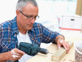 Mature carpenter drilling a hole in wood Stock Photography
