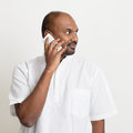 Mature casual business indian man talking on phone portrait of calling smartphone standing plain background with shadow Royalty Free Stock Photography