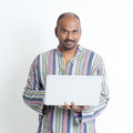 Mature casual indian man using laptop portrait of business computer standing on plain background with shadow Royalty Free Stock Photo