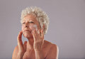Mature caucasian woman applying anti wrinkle face cream portrait of senior lotion on her against grey background Royalty Free Stock Photo