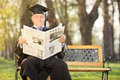 Mature college professor reading newspaper in park outdoors Royalty Free Stock Photography