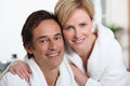 Mature couple in bathrobes smiling Royalty Free Stock Images