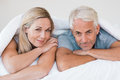 Mature couple in bed senior romantic under a white duvet the happy lying down their and looking at camera retired Stock Images
