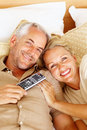 Mature couple on the bed watching TV Royalty Free Stock Photo