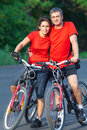Mature couple on bicycle happy riding a in the green park Stock Images
