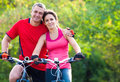 Mature couple on bicycle happy riding a in the green park Royalty Free Stock Images