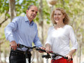 Mature couple with bicycles positive senior smiling in public garden Stock Photo