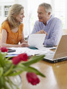 Mature couple with bills calculator and laptop smiling looking at Royalty Free Stock Images