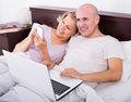 Mature couple burring with laptop in bedroom interior Royalty Free Stock Photos