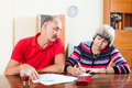 Mature couple calculating family budget at home interior Stock Photography