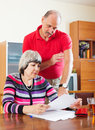 Mature couple calculating family budget serious at home Stock Image
