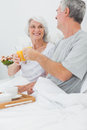 Mature couple clinking their orange juice glasses while they are having breakfast in bed Stock Photo