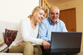 Mature couple with computer at table at home Stock Images