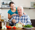 Mature couple cooking food together smiling in kitchen Royalty Free Stock Photos