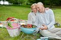 Mature couple cooking on an outdoor picnic in casual wear meat and chilies a portable barbecue at in forest park Royalty Free Stock Image