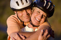 Mature couple in cycling helmets standing on mountain trail man embracing woman smiling close up portrait men Stock Photos