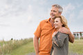 Mature couple daydreaming portrait of a happy man embracing her wife and contemplate the future Stock Image