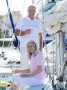 Mature couple on deck of boat with drinks, smiling, portrait Royalty Free Stock Photo