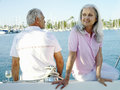 Mature couple on deck of boat smiling Stock Images