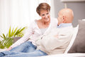 Mature couple discussing together with love old women and old men happy because they each other in a living room on a sofa Stock Images